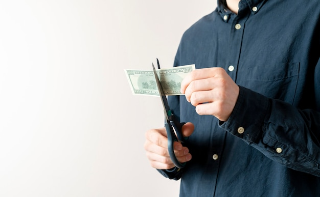 破産とビジネスの問題の象徴として私たち百ドルの現金紙幣を切る人の手