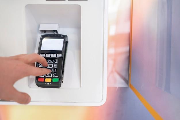 사람의 손이 비밀번호를 입력하고 버튼을 눌러 결제합니다.