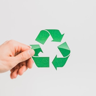 A person's hand holding green recycle symbol on white backdrop