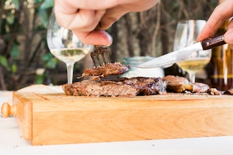 A person's hand holding knife and fork cutting grilled beef steak on chopping board