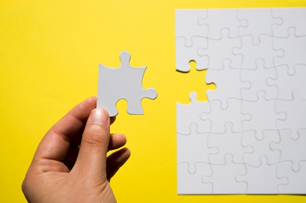노란색 배경 위에 누락 된 흰색 직소 퍼즐 조각을 들고 사람의 손