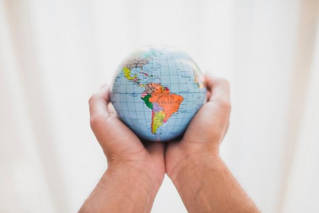 작은 지구본을 들고 사람의 손