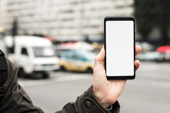 A person's hand holding smart phone showing white blank screen against blurred road