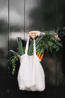 A person's hand holding white grocery bag filled with vegetables