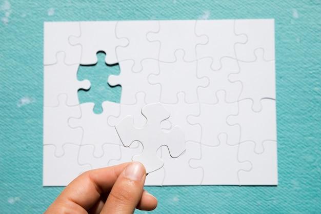 파란색 질감 된 배경 위에 퍼즐 격자에 흰색 퍼즐 조각을 들고 사람의 손