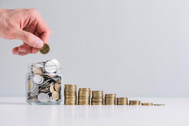 Рука человека кладет деньги в стеклянную банку возле уменьшенных уложенных монет