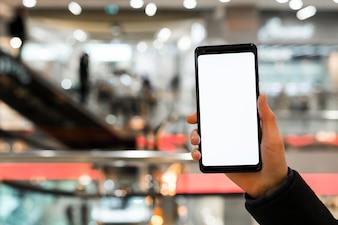 Рука человека показывает экран мобильного телефона в торговом центре