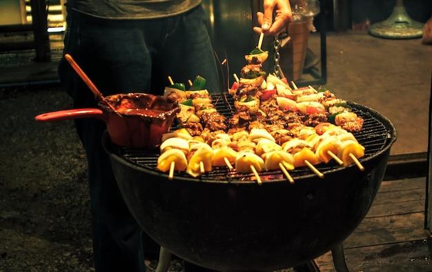 バーベキューの上にグリルステーキにソースを広げている人の手。夏または春の屋外バーベキューテーブルの木製まな板に口の水まきグルメバーベキューを閉じます。