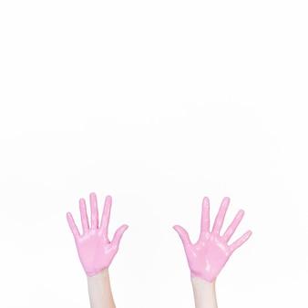 白い背景にピンクの塗料で手を示す人
