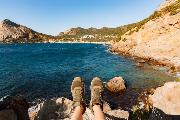 절벽에 앉아있는 사람 얼굴 여행자의 발 셀카입니다. 녹색 운동화에 다리의 셀카입니다. 백그라운드에서 바위와 바다 크림의 여름 시간