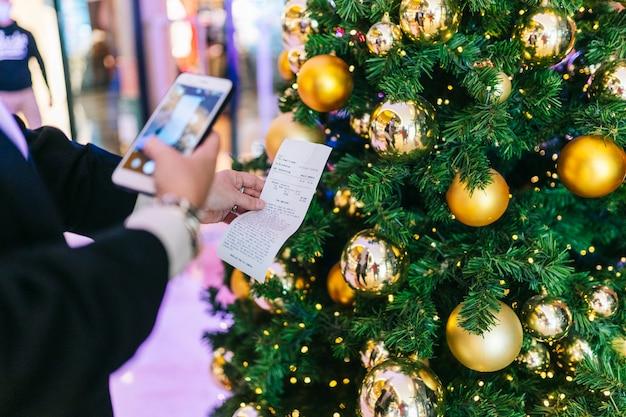 한 사람이 크리스마스 트리가있는 전화기로 티켓 사진을 찍습니다.