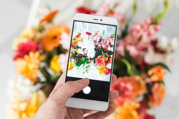 Человек с фотографией букета цветов со смартфоном