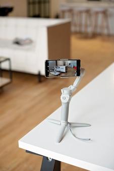 사람은 안정 장치가있는 전화기를 사용하여 현대적인 인테리어에서 실시간으로 사진과 동영상을 찍습니다.