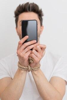 スマートフォンのインターネット中毒またはソーシャルメディア中毒を持って手を縛られている人
