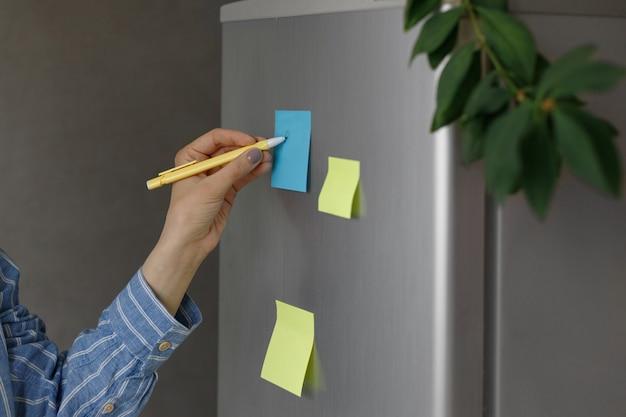 Человек пишет ручкой на наклейке на холодильнике дома желтые и синие наклейки