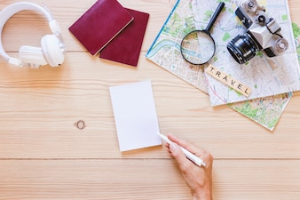 A person writing on paper with traveler accessories on wooden background