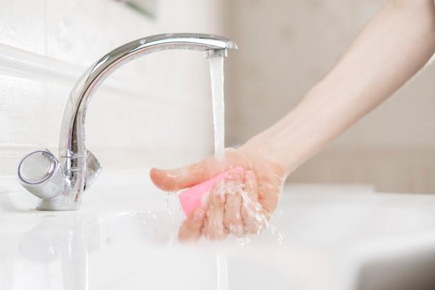 個人の衛生規則、石鹸のレンガ片を持っていて汚れた手を洗う人、コロナウイルス感染症の保護