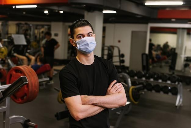 개인 트레이너는 보호 마스크를 쓰고 체육관 배경에 서 있습니다.