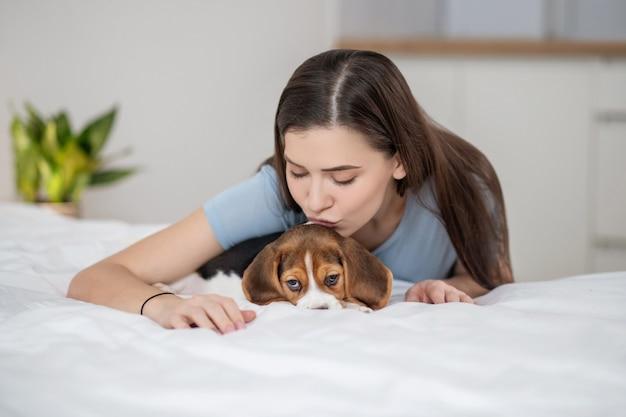 Владелец домашнего животного сидит на кровати и чувствует себя счастливым со своим питомцем