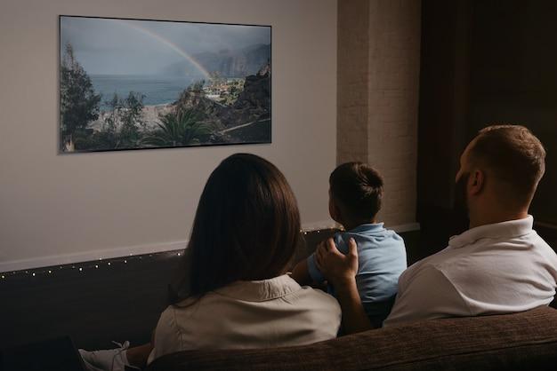 소파에 놓인 와이드 스크린 tv로 영화를보고있는 아버지, 아들, 젊은 어머니의 뒤에서 찍은 사진