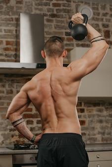 アパートで黒いおもりを押している筋肉質の男性の後ろからの写真