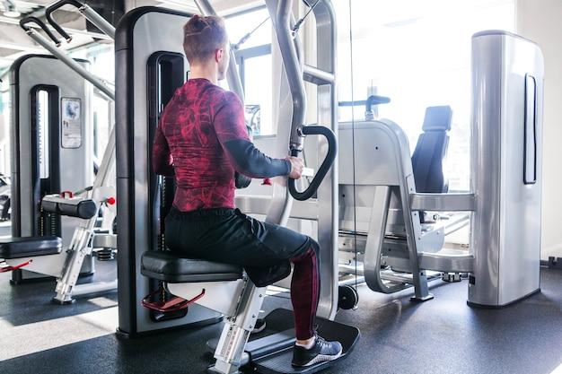 Фотография со спины спортивного мускулистого мужчины в красно-черной блузке, который занимается на тренажере. горизонтальная рамка