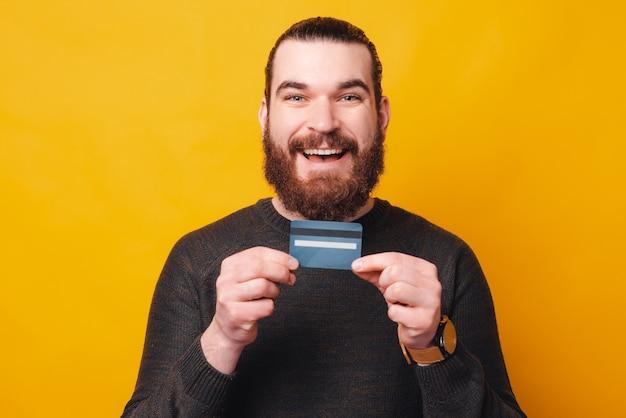 何かを買う準備ができているクレジットカードを持っているひげを生やした男の写真