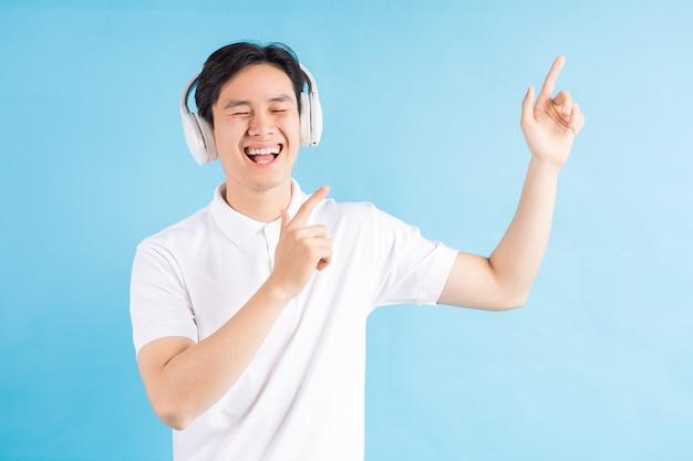 音楽を聴いて音楽をフォローしているハンサムなアジアの少年の写真