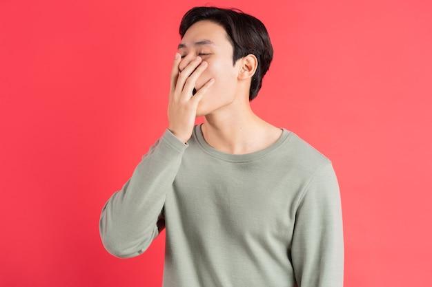彼の口の上に彼の手であくびをしているハンサムなアジア人の写真