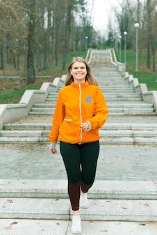 Фотография счастливой молодой спортсменки, бегающей утром с улыбкой на лице в парке