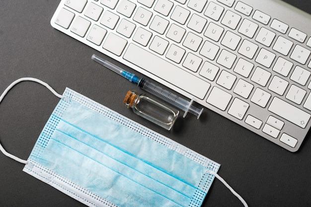 暗い机の上のマスク、ワクチン、キーボードの写真