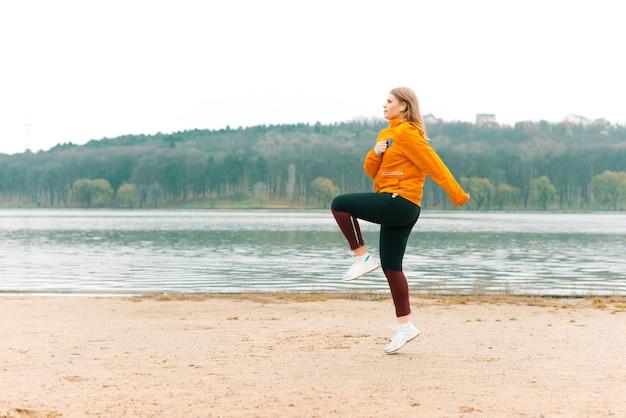 Фотография молодой женщины, делающей зарядку утром на пляже у озера