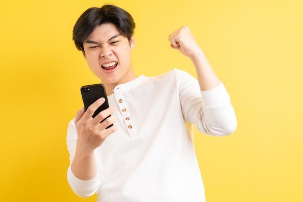 彼の携帯電話を見て、勝利の表情を示しているアジア人の男性の写真