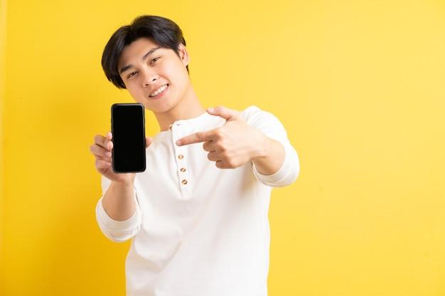 空白の画面で携帯電話を指しているアジア人男性の写真
