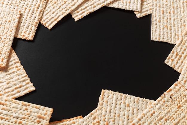 검은 배경에 matzah 또는 matza 조각의 사진. 유대인의 유월절 휴일을 위한 matzah. 텍스트를 위한 장소, 복사 공간