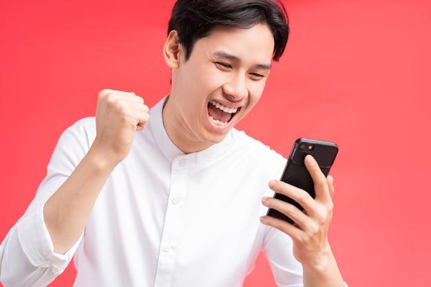 彼が彼の携帯電話でテキストメッセージを受け取ったときに彼の勝利を祝っている男の写真