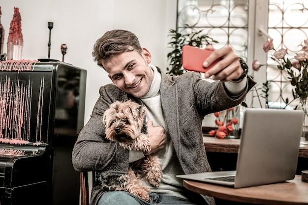 フォトジェニックな犬。犬と一緒に自分撮りをする男