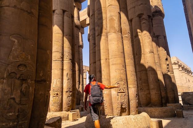 エジプト、ルクソール神殿の柱にある古代エジプトの絵を見ている写真家