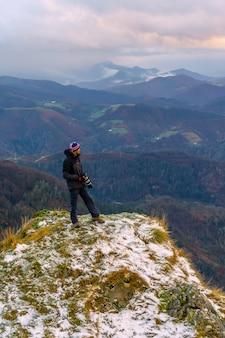 スペイン、サンセバスチャン近くのオイアルツンの町にあるペーニャスデアヤ山で、雪をかぶった山頂の景色を見ている写真家
