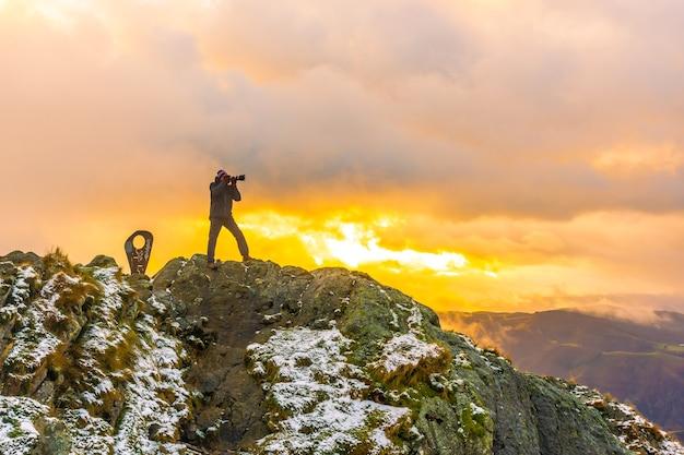 スペイン、サンセバスチャン近くのオイアルツンの町のペーニャスデアヤ山にある、雪の降る冬のオレンジ色の夕日の山の頂上にいる写真家