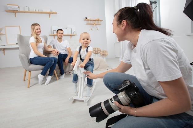 Фотограф снимает семью в фотостудии.