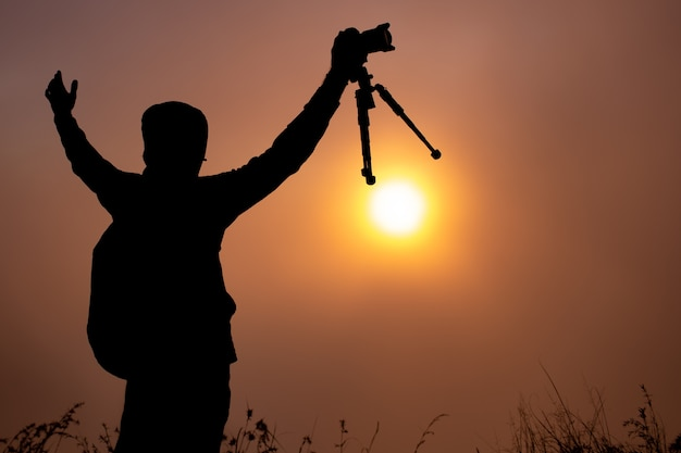 Фотограф фотографирует рассвет солнца на вулкане батур. бали индонезия