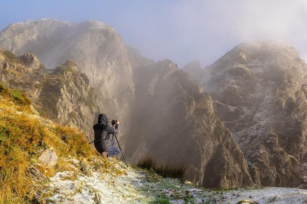 スペイン、サンセバスチャン近くのオイアルツンの町にあるペーニャスデアヤの山で、雪の降る冬の日没で三脚を使って写真を撮る写真家
