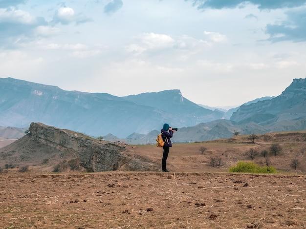 大きなカメラを持った写真家が美しい山の風景を撮影します。