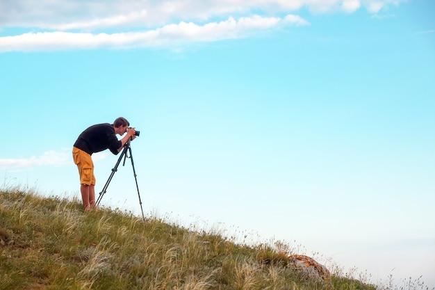 삼각대와 카메라를 가진 사진가가 산의 풍경 사진을 찍습니다. 일하는 사람.