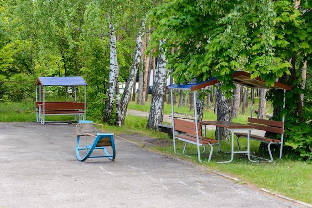 Площадка для пикника с видом на волгу на фоне деревьев. пикник в зеленой зоне. место для отдыха уставших ходунков, стол, скамейки. место для барбекю.