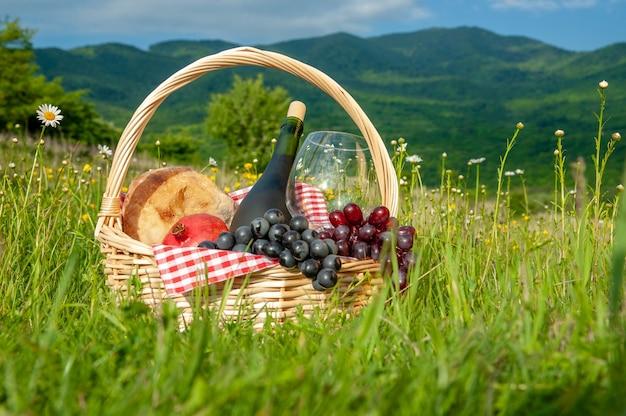 緑の芝生の牧草地にワイン、フルーツ、ブドウ、パンが入ったピクニックバスケットが立っています