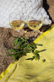 白ワイン、オリーブの枝、砂浜の黄色い毛布に籐の袋を持った砂浜でのピクニック。