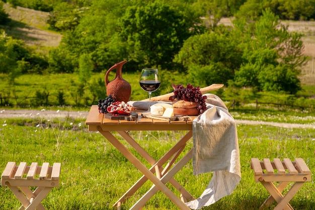 緑の草の牧草地に赤ワイン、チーズ、果物、ブドウ、パンがセットされたピクニックテーブルが立っています