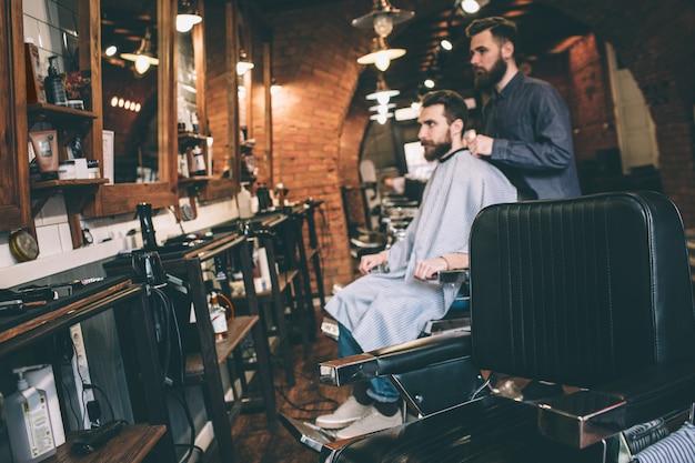 Картинка на расстоянии. парень сидит в кресле и готовится стричь бороду. его парикмахер готов начать работу.